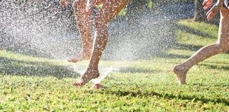 Παιχνίδι νέων κοριτσιών που πηδά σε έναν ψεκαστήρα χορτοταπήτων νερού κήπων Στοκ εικόνα με δικαίωμα ελεύθερης χρήσης