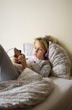 Παιχνίδι νέων κοριτσιών στο κινητό τηλέφωνό της στο κρεβάτι Στοκ Εικόνα