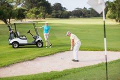 Παιχνίδι παικτών γκολφ στην παγίδα άμμου από τη γυναίκα Στοκ εικόνα με δικαίωμα ελεύθερης χρήσης
