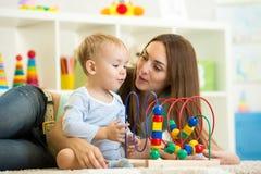 Παιχνίδι παιδιών και μητέρων με το εκπαιδευτικό παιχνίδι Στοκ φωτογραφία με δικαίωμα ελεύθερης χρήσης