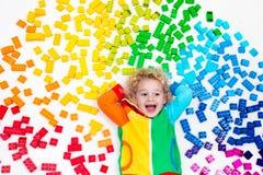 Παιχνίδι παιδιών με το πλαστικό παιχνίδι φραγμών ουράνιων τόξων Στοκ Εικόνες