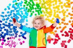 Παιχνίδι παιδιών με το πλαστικό παιχνίδι φραγμών ουράνιων τόξων Στοκ Εικόνα