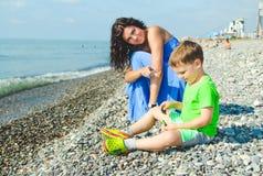 Παιχνίδι παιδιών στην παραλία πετρών Μητέρα που παρουσιάζει στη κάμερα Στοκ φωτογραφία με δικαίωμα ελεύθερης χρήσης