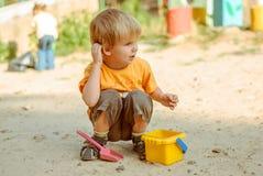 παιχνίδι παιδιών στο κιβώτιο άμμου Στοκ Εικόνες