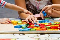 Παιχνίδι παιδιών χεριών με τους φραγμούς κατασκευής Στοκ Εικόνες
