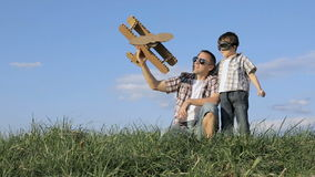 Παιχνίδι πατέρων και γιων με το αεροπλάνο παιχνιδιών χαρτονιού στο πάρκο α απόθεμα βίντεο