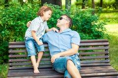 Παιχνίδι πατέρων και γιων στο πάρκο στον πάγκο στο χρόνο ημέρας Στοκ φωτογραφία με δικαίωμα ελεύθερης χρήσης