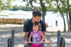 Παιχνίδι πατέρων και κοριτσάκι στο πάρκο Στοκ Φωτογραφίες