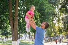 Παιχνίδι πατέρων και κορών έξω στο πάρκο στοκ εικόνες