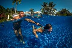 Παιχνίδι πατέρων και κορών σε μια πισίνα Στοκ Εικόνες