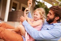 Παιχνίδι πατέρων με την κόρη σε μια ταλάντευση σχοινιών σε έναν κήπο Στοκ Εικόνα