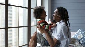 Παιχνίδι πατέρων χαμόγελου με τον ευτυχή γιο στο σπίτι απόθεμα βίντεο