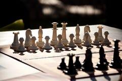 Παιχνίδι σκακιού Άσπρα και μαύρα κομμάτια σκακιού στον πίνακα Στοκ Φωτογραφίες