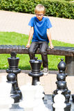 Παιχνίδι σκακιού με το γιγαντιαίο κομμάτι σκακιού Αγόρι που παίζει το στρατηγικό υπαίθριο παιχνίδι στο γραπτό πίνακα Στοκ φωτογραφία με δικαίωμα ελεύθερης χρήσης
