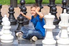 Παιχνίδι σκακιού με το γιγαντιαίο κομμάτι σκακιού Αγόρι που παίζει το στρατηγικό υπαίθριο παιχνίδι στο γραπτό πίνακα Στοκ Εικόνα