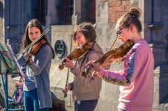 Παιχνίδι τριών ευτυχές θηλυκό βιολιστών εφήβων για τη δωρεά στοκ φωτογραφία με δικαίωμα ελεύθερης χρήσης