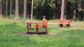 Παιχνίδι τριών ευτυχές παιδιών στη διασταύρωση κυκλικής κυκλοφορίας στο πράσινο πάρκο φιλμ μικρού μήκους