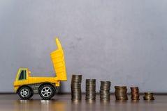 Παιχνίδι φορτηγών απορρίψεων που μεταφορτώνει έναν σωρό νομισμάτων Στοκ Φωτογραφίες