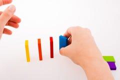 Παιχνίδι χεριών με το χρωματισμένο ντόμινο Στοκ Εικόνα