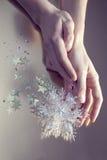 Παιχνίδι Χριστουγέννων στα όμορφα χέρια στο υπόβαθρο Στοκ Εικόνες