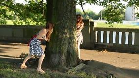 Παιχνίδι δύο το νέο χαριτωμένο κοριτσιών εφήβων επιτρέπει το πάρκο, τρέχει γύρω από το δέντρο φιλμ μικρού μήκους