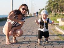 Παιχνίδι Mom και γιων κοντά στον ωκεανό στο ηλιοβασίλεμα Σε μια πολύ όμορφη αστεία έκφραση του προσώπου μωρών Στοκ Εικόνα