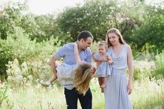 Παιχνίδι Mom και μπαμπάδων στη φύση και αγκάλιασμα δύο κορών Στοκ Εικόνα