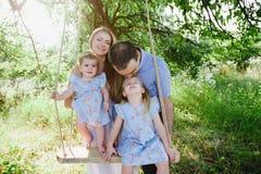Παιχνίδι Mom και μπαμπάδων στη φύση και αγκάλιασμα δύο κορών Στοκ φωτογραφία με δικαίωμα ελεύθερης χρήσης