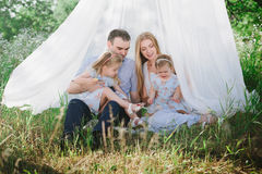 Παιχνίδι Mom και μπαμπάδων στη φύση και αγκάλιασμα δύο κορών Στοκ Εικόνες