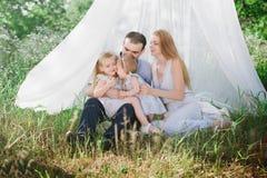 Παιχνίδι Mom και μπαμπάδων στη φύση και αγκάλιασμα δύο κορών Στοκ Φωτογραφία