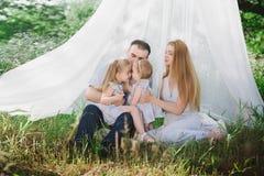 Παιχνίδι Mom και μπαμπάδων στη φύση και αγκάλιασμα δύο κορών Στοκ Φωτογραφίες