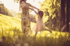 Παιχνιδιάρικα στη φύση Μικρό κορίτσι με τη μητέρα της Στοκ Φωτογραφία