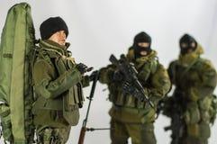 Παιχνιδιών ατόμων στρατιωτών δράσης άσπρο υπόβαθρο μεταξιού αριθμού μικροσκοπικό ρεαλιστικό Στοκ Φωτογραφίες