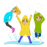 Παιδάκια που παίζουν στη λακκούβα που φορά τα ζωηρόχρωμες αδιάβροχα και τις μπότες Στοκ Φωτογραφία