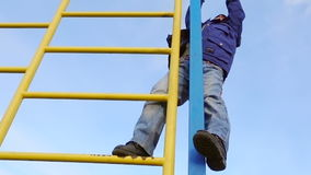 Παιδάκι που αναρριχείται στη σκάλα στην παιδική χαρά απόθεμα βίντεο
