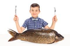 Παιδάκι που κάθεται στον πίνακα με ένα τεράστιο ακατέργαστο ψάρι Στοκ φωτογραφία με δικαίωμα ελεύθερης χρήσης