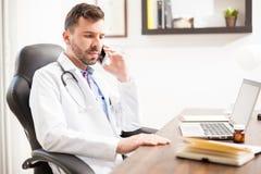 Παιδίατρος που μιλά στο τηλέφωνο σε ένα γραφείο Στοκ φωτογραφία με δικαίωμα ελεύθερης χρήσης