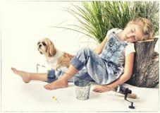 Παιδί ή νέο κορίτσι με το σκυλί της που παίρνει ένα NAP ή που κοιμάται ενώ στοκ εικόνα με δικαίωμα ελεύθερης χρήσης