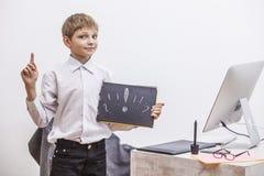 Παιδί αγοριών με έναν υπολογιστή, στο γραφείο σε ένα άσπρο busine πουκάμισων Στοκ Φωτογραφίες