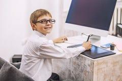 Παιδί αγοριών με έναν υπολογιστή, στο γραφείο σε ένα άσπρο busine πουκάμισων στοκ εικόνα