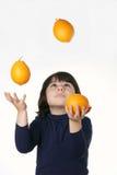 Παιδί ζογκλέρ με τα πορτοκάλια Στοκ Εικόνες