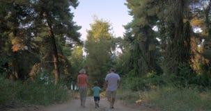 Παιδί και παππούδες και γιαγιάδες που τρέχουν στο δάσος απόθεμα βίντεο