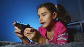 Παιδί κοριτσιών εφήβων που παίζει το φορητό τηλεοπτικό παιχνίδι online ένα παιδί κονσολών τη νύχτα στο εσωτερικό απόθεμα βίντεο