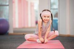 Παιδί κοριτσιών που κάνει τις ασκήσεις ικανότητας στη λέσχη υγείας, που τεντώνει στην άσκηση στοκ εικόνες