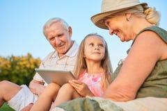 Παιδί με μια ταμπλέτα, παππούδες και γιαγιάδες στοκ εικόνα
