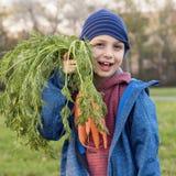 Παιδί με τα καρότα στον κήπο στοκ φωτογραφία