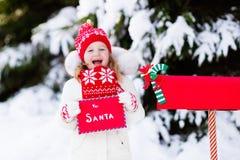 Παιδί με την επιστολή σε Santa στην ταχυδρομική θυρίδα Χριστουγέννων στο χιόνι Στοκ Φωτογραφία
