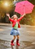 Παιδί με την ομπρέλα σημείων Πόλκα που φορά τις κόκκινες μπότες βροχής Στοκ φωτογραφία με δικαίωμα ελεύθερης χρήσης