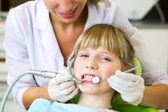 Παιδί με την παραλαβή στην υποδοχή οδοντιάτρων στο dentistClose επάνω στο πορτρέτο χαμογελώντας του λίγο κοριτσιού στον οδοντίατρ Στοκ Φωτογραφίες