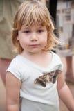 Παιδί με την πεταλούδα Samia Ricini σκώρων στο πουκάμισό της Στοκ Εικόνες